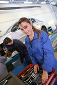 Smiling young woman in auto mechanics training class