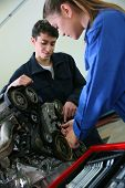 Students in mechanics working on car engine