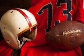 A grouping of vintage, antique american football items including an helmet, jersey, and old leather