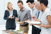 stock photo of buffet catering  - Business Colleagues Eating Meal Together In Restaurant - JPG