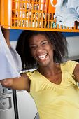 Portrait of happy young woman carrying basket of clothes in laundromat
