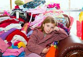 stock photo of laundry  - Blond kid girl sitting on a messy clothes sofa before folding laundry - JPG