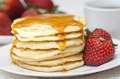 foto of maple syrup  - A stack of pancakes with syrup and fresh strawberries - JPG