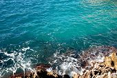 stock photo of blue  - Azure water south sea lapping at the rocky shore - JPG
