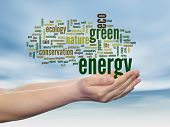 Concept or conceptual abstract green ecology and energy word cloud text in man hand, blue sky backgr
