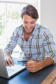 Smiling casual man using laptop to shop online at home in the living room
