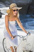 Beautiful smiling blonde in sundress on bike at the beach on a sunny day
