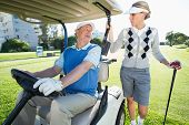 stock photo of buggy  - Happy golfing couple setting out for the day on buggy on a sunny day at the golf course - JPG