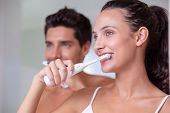 Attractive couple brushing their teeth in the morning at home in bathroom