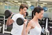 Fit couple lifting barbells together at the gym