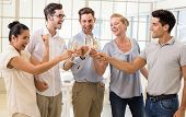 Casual business team celebrating with champagne in the office