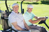 stock photo of buggy  - Golfing friends driving in their golf buggy smiling at camera on a sunny day at the golf course - JPG