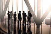 Composite image of business colleagues standing in large room overlooking city