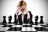 Composite image of redhead businesswoman with head in hands with chessboard