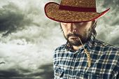 image of wrangler  - Farmer with cowboy hat and wheat straw in his mouth - JPG