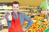 Happy salesman congratulates with his thumbs up in a supermarket