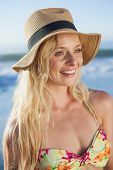 Gorgeous blonde in straw hat smiling on beach on a sunny day