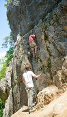 picture of climbing wall  - a young man climbing a rock wall - JPG