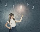Little cute girl and electric bulbs hanging above