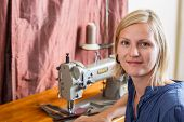 Smiling Blonde Woman At Sewing Machine