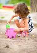 Cute little girl is playing with sand in playground, outdoor shoot