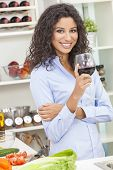 Beautiful young Latina Hispanic woman smiling, relaxing and drinking a glass of red wine in her kitc