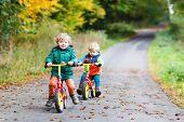 stock photo of four-wheel drive  - Two active brother boys having fun on bikes in autumn forest - JPG
