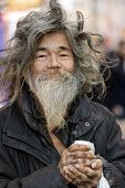 TOKYO,JAPAN, November 25 : Cheerful tramp  holding a drink can, posing in the street near the Shibuy