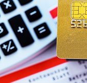 a golden credit card, bank statement and calculator. symbolic photo for cashless purchases and statu