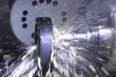 stock photo of auger  - Gorizontal mill cutting the metal blank with cooling liquid - JPG