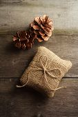 Still life of burlap wrapped present with pine cones