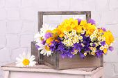 Beautiful flowers in crate on light background