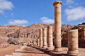 PETRA, JORDAN - MARCH 15, 2014: Tourists on the Colonnaded street of Petra against ancient Nabataean