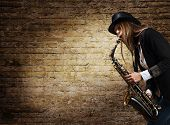 foto of saxophones  - young beautiful woman in black hat with saxophone - JPG