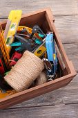 Wooden box with different tools, on wooden background