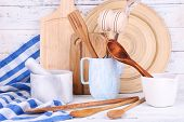 Composition of wooden cutlery, mortar, bowl and cutting board on wooden background