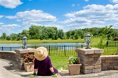 foto of recliner  - Senior lady gardener taking a break to admire the view from her front patio over a lake and lush green countryside sitting with her back to the camera in a straw sunhat - JPG