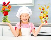 little girl dressed as a cook balanced pyramid of vegetables and fruits