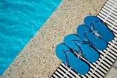 Flip Flop on Wood Floor pool edge with surface of water background