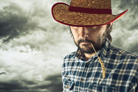 stock photo of wrangler  - Farmer with cowboy hat and wheat straw in his mouth - JPG