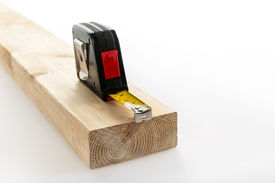 picture of 2x4  - Metal imperial metric tape measure measuring two by four lumber on white background - JPG