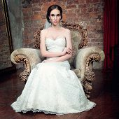 Bride In Wedding Dress And Veil In A Chair