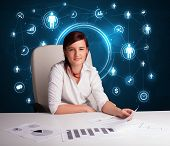 Young businesswoman sitting at desk with social network icons