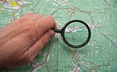 Hand With Magnifying Glass Above A Map