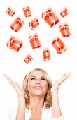 Portrait of cute cheerful woman catching Christmas gifts isolated on white background, having fun in festive day, enjoying surprises
