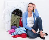 image of dirty-laundry  - Tired housewife is doing laundry with washing machine at home - JPG