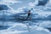 Woman running against blue sky