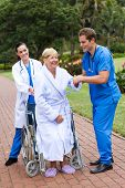 nurse and doctor helping patient to walk