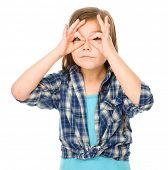 Portrait of a cute little girl showing aviator sign, isolated over white