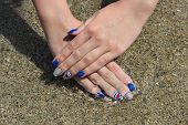 stock photo of nail paint  - Finger nail treatment hands with painted fingernails at sand in water - JPG